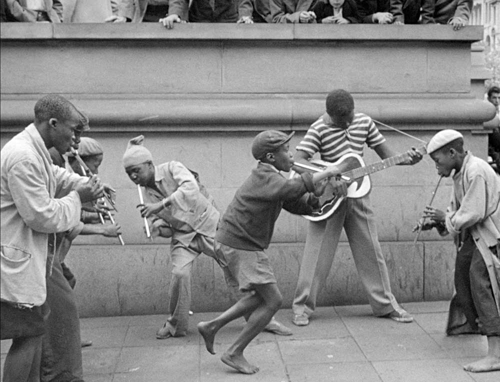 Penny Whistlers and Musicians on the street in the film COME BACK, AFRICA by Lionel Rogosin. The South African anti-apartheid classic from 1959 is a Milestone Film & Video release. Restored by the Cineteca di Bologna and the laboratory L'Imagine Ritrovata with the collaboration of Rogosin Heritage and the Anthology Film Archives.